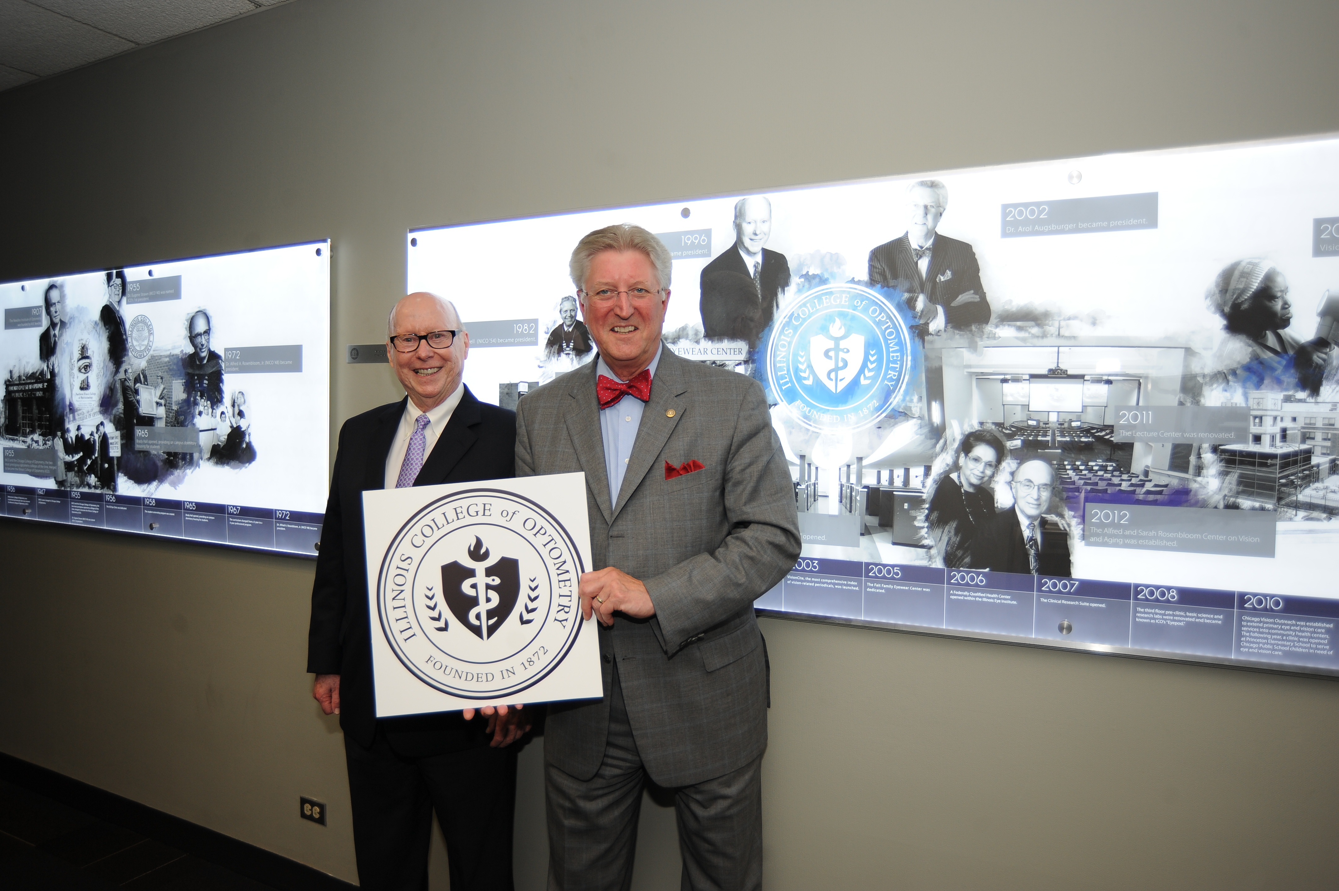 President of Illinois College of Optometry (ICO) Arol Augsburger (in bow tie) stands with his ICO President predecessor Dr. Charles Mullen in front of a mural depicting key events in the 144 year history of ICO.