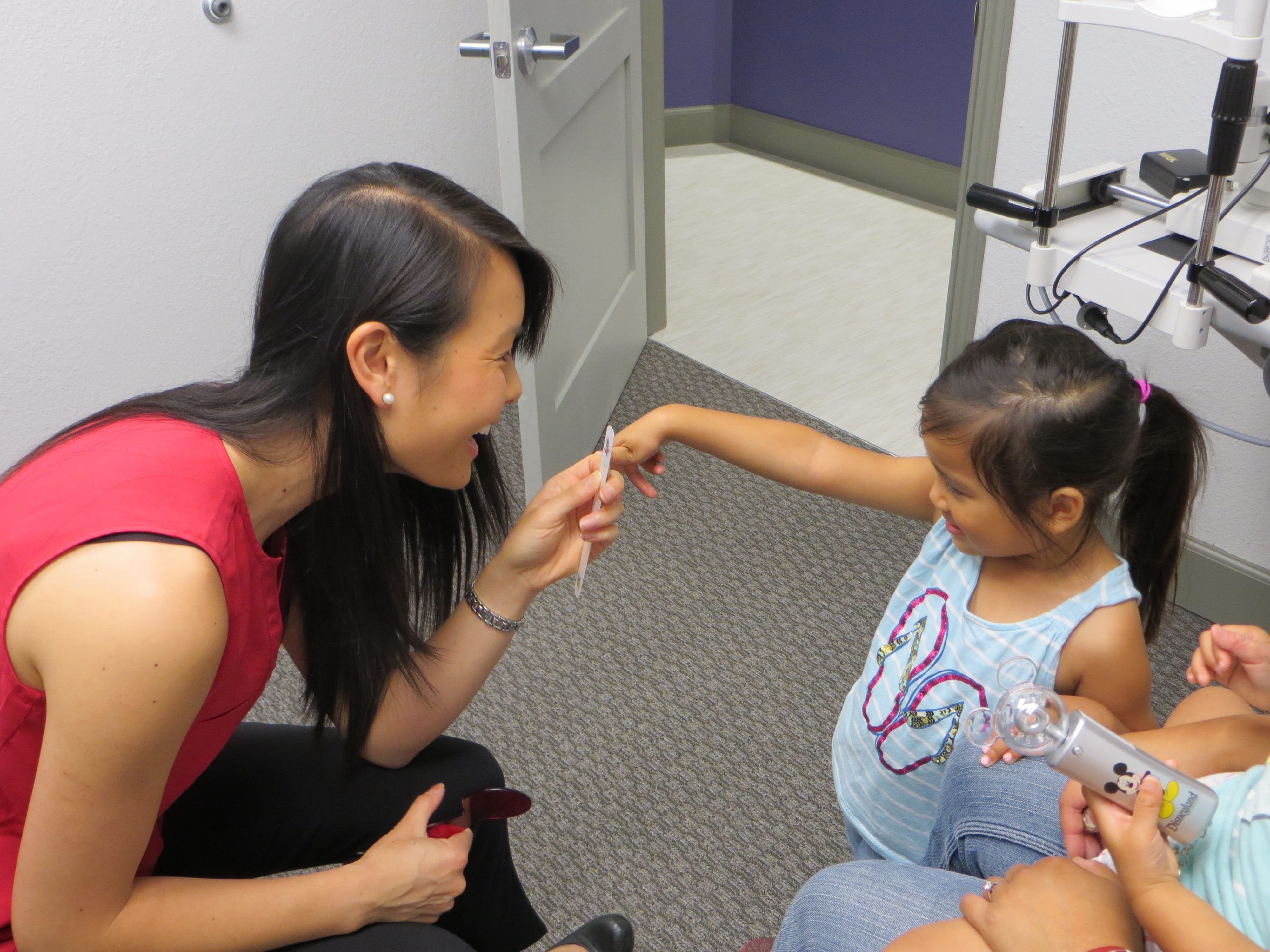 Dr. Valerie Lam engages a young patient in order to check convergence and perform a cover test.